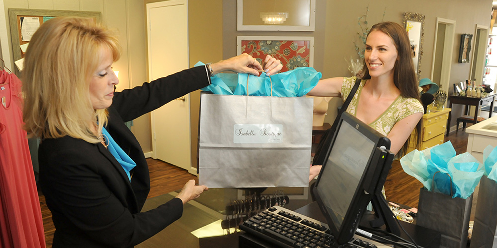 Photo of Isabella Boutique team member Tammy handing a customer a shopping bag